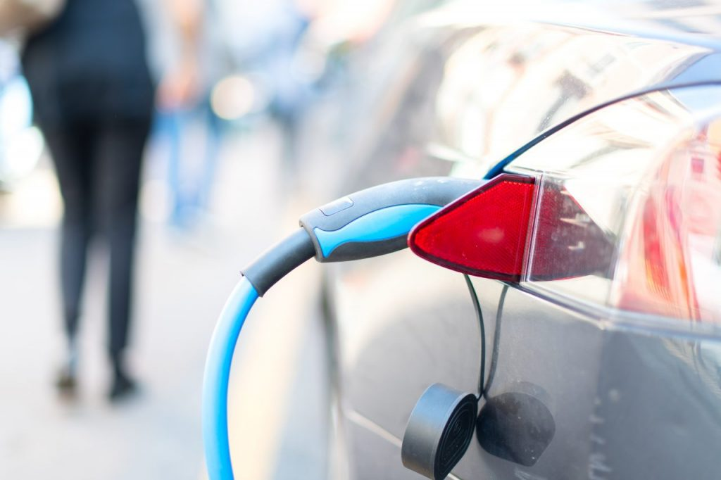 an-electric-car-is-charged-RJUMPD8